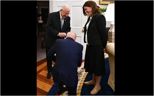 Le président américain Joe Biden s'agenouille devant Rivka Ravitz, chef de cabinet du président israélien Reuven Rivlin, après avoir appris qu'elle avait 12 enfants. (Haim Zach/GPO)