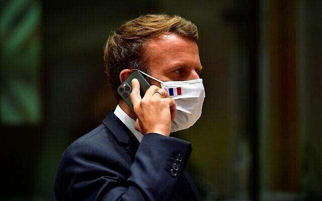 Le président français Emmanuel Macron parle sur son téléphone portable pendant une table ronde lors d'un sommet de l'UE à Bruxelles, le 20 juillet 2020. (Crédit : John Thys, Pool Photo via AP)