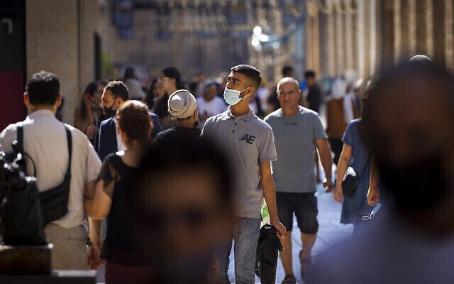 Des personnes sont vues avec et sans masque de protection à Jérusalem, le 8 juillet 2021. (Crédit: Olivier Fitoussi/Flash90)