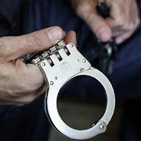 Illustration : Un policier tient des menottes. (Yossi Zamir/Flash90)
