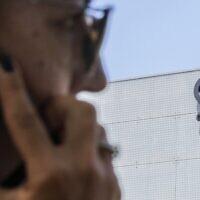 Sur cette photo d'archive prise le 28 août 2016, une Israélienne utilise son iPhone devant le bâtiment abritant le groupe israélien NSO, à Herzliya, près de Tel Aviv. (Jack Guez/AFP)