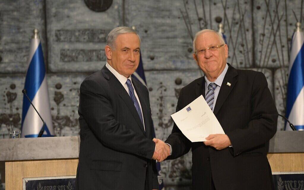 Le président Reuven Rivlin remet au Premier ministre Benjamin Netanyahu le mandat pour former un gouvernement, le 25 mars 2015. (Crédit : Amos Ben Gershom/GPO)