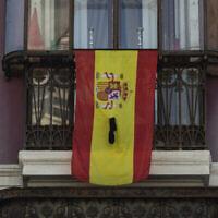 Un drapeau espagnol sur un rebord de fenêtre avec un ruban noir à Madrid, le 12 avril 2020. (AP Photo/Bernat Armangue)