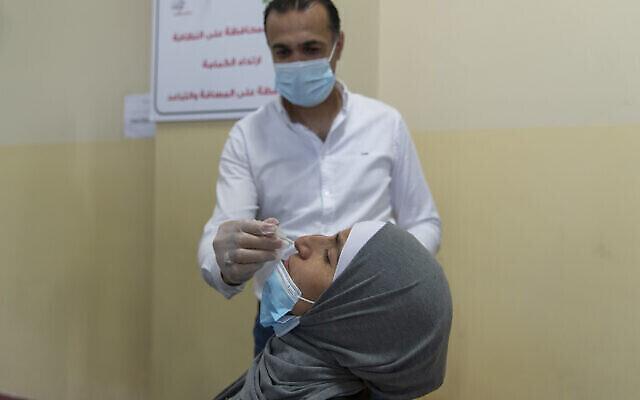Un agent de santé prélève un échantillon nasal sur une femme palestinienne dans un centre de dépistage du COVID-19, dans la ville de Ramallah, en Cisjordanie, le dimanche 6 juin 2021. (Crédit: AP Photo/Nasser Nasser)