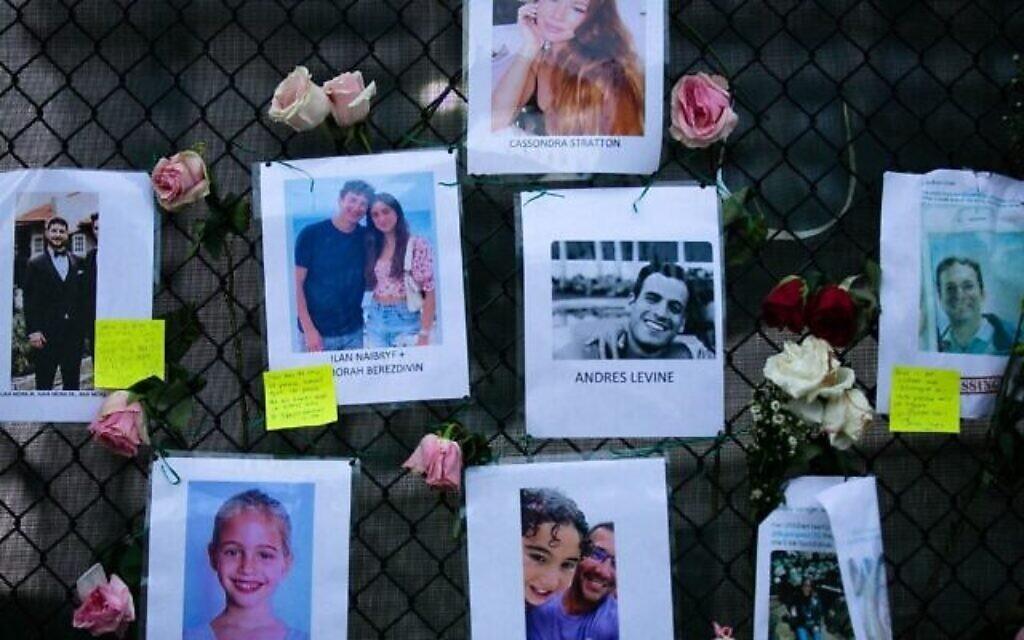 Des photos d'Andres Levine, Ilan Naibryf et Deborah Berezdivin, trois des victimes juives de l'effondrement de l'immeuble de Surfside, au centre parmi d'autres photos des disparus affichées sur un mémorial de fortune sur le site de l'immeuble à Surfside, en Floride, le 26 juin 2021. (Crédit : Andrea Sarcos/AFP)