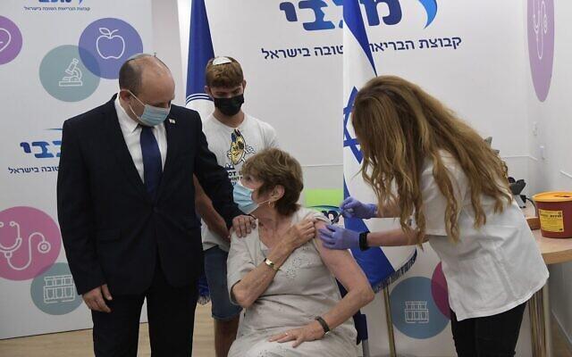 Le Premier ministre Naftali Bennett accompagne sa mère, Myrna, se faire administrer un rappel contre la COVID-19, le 3 août 2021. (Crédit : Kobi Gideon/GPO)