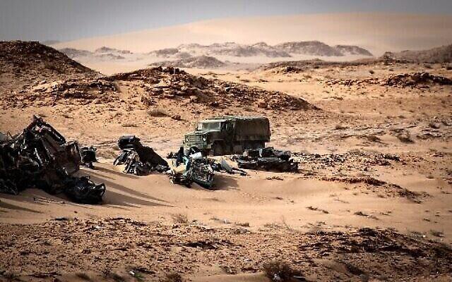 Un véhicule de l'armée marocaine passe devant des épaves de voitures à Guerguerat, au Sahara occidental, le 24 novembre 2020, après l'intervention des forces armées royales marocaines dans la région. (Crédit : Fadel SENNA / AFP)