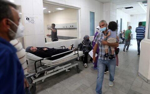 Une patiente gît dans un lit dans un couloir de l'hôpital universitaire Rafic Hariri à Beyrouth, la capitale du Liban, le 23 juillet 2021. (Crédit : STR/AFP)