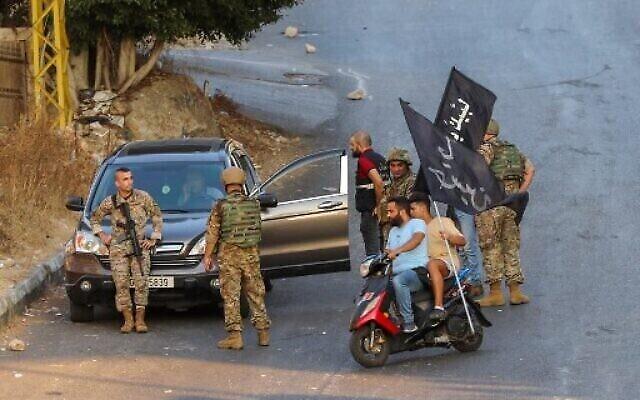 Des partisans du Hezbollah portent des drapeaux sur des motos devant des soldats libanais alors que l'armée se déploie au milieu d'affrontements dans la région de Khalde, au sud de la capitale, le 1er août 2021 (Crédit : ANWAR AMRO / AFP).