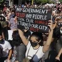 Un manifestant marche avec une pancarte indiquant en anglais « mon gouvernement a tué mon peuple, a pris nos maisons et a réduit notre ville en poussière » dans le quartier de Gemmayze alors que les manifestants se dirigent vers le port de la capitale libanaise le 4 août 2021, à l'occasion du premier anniversaire de l'explosion qui a ravagé le port et la ville. (Crédit :  JOSEPH EID / AFP)