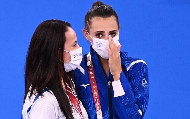 L'Israélienne Linoy Ashram, au centre, avec son entraîneur après sa victoire en finale de l'épreuve de gymnastique rythmique  aux Jeux olympiques 2020 de Tokyo, le 7 août 2021. (Crédit :  Martin Bureau / AFP)