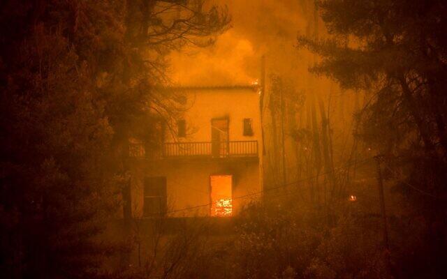 Une maison en feu alors que l'incendie d'une forêt se rapproche du village de  Pefki sur l'île d'Eubée, la deuxième île la plus grande de Grèce, un feu qui serait lié au changement climatique, le 8 août 2021. (Crédit : ANGELOS TZORTZINIS / AFP)