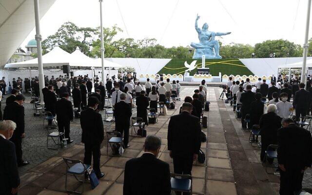Les participants prient lors d'un service commémoratif pour les victimes du bombardement atomique américain au parc de la paix à Nagasaki, le 9 août 2021, alors que la ville marque le 76e anniversaire du bombardement. (Crédit : par STR / JIJI PRESS / AFP) / Japon OUT