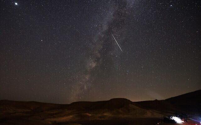 La Voie lactée traversée par une météorite au-dessus du désert du Negev, près de la ville israélienne de Mitzpe Ramon, le 13 août 2021. (Crédit : Menahem KAHANA / AFP)