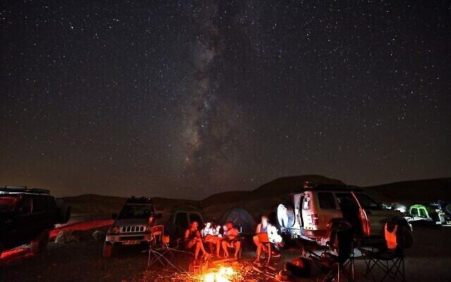 Des campeurs sous la Voie lactée, au dessus du désert du Negev, à proximité de Mitzpe Ramon, le 13 août 2021. (Crédit :Menahem KAHANA / AFP)