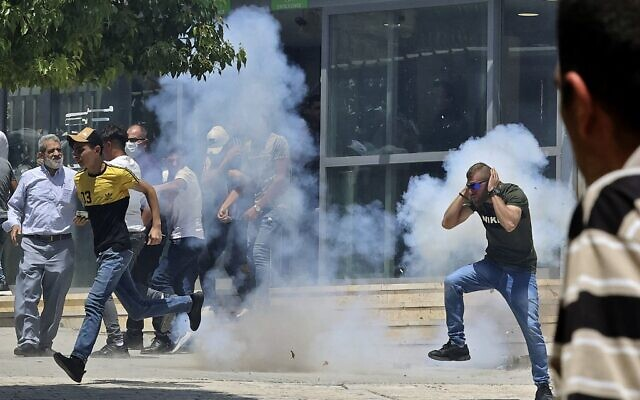 Des manifestants palestiniens courent pour éviter les gaz lacrymogènes pendant des affrontements avec les forces israéliennes de sécurité lors d'une manifestation qui a eu lieu après la prière du vendredi à la mosquée Ibrahimi (Tombeau des patriarches), le 13 août 2021. (Crédit : HAZEM BADER / AFP)