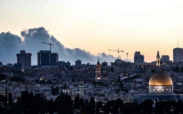 Une photo prise depuis le mont des Oliviers montre la Vieille Ville et le Dôme du rocher avec, à l'arrière, un nuage de fumée provenant d'un important feu de forêt, le 15 août 2021. (Crédit :  Ahmad GHARABLI / AFP)