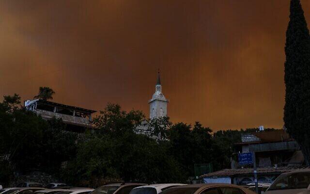 De la fumée et des flammes provenant d'un feu de forêt près du village israélien de Moshav Shoresh, le 15 août 2021. (Crédit : Menahem KAHANA / AFP)