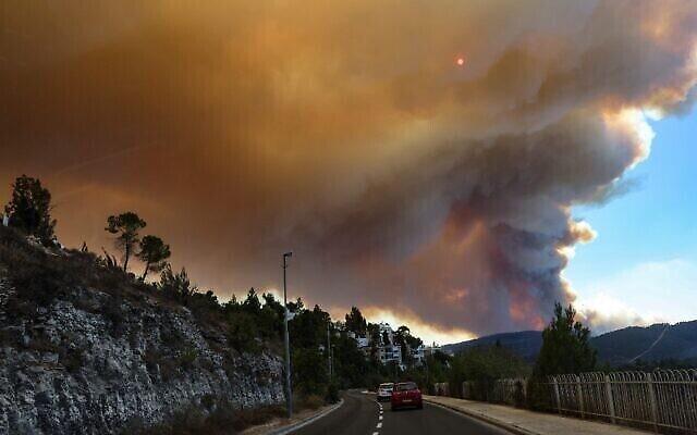 Des voitures circulent alors que des flammes et de la fumée s'élèvent suite à un feu de forêt sur les montagnes de Jérusalem, près du village du Moshav Shoresh, le 15 août 2021. (Crédit :Menahem KAHANA / AFP)