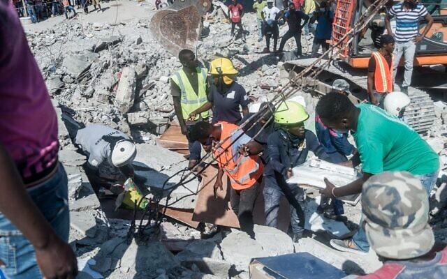 Des Haïtiens recherchent des survivants parmi les décombres dans le quartier de Dexia 6, aux Cayes, à Haïti, le 15 août 2021, après qu'un séisme de magnitude 7,2 a frappé la péninsule sud-ouest du pays. (Crédit : Réginald LOUISSAINT JR / AFP)