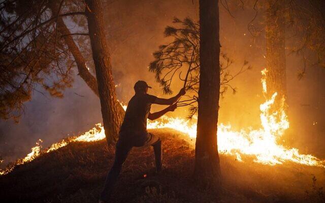 Un Marocain tente d'éteindre un incendie alors que des incendies sauvages ont détruit quelque 200 hectares de forêt dans la région de Chefchaouen, dans le nord du Maroc, le 15 août 2021. (Crédit : FADEL SENNA / AFP)