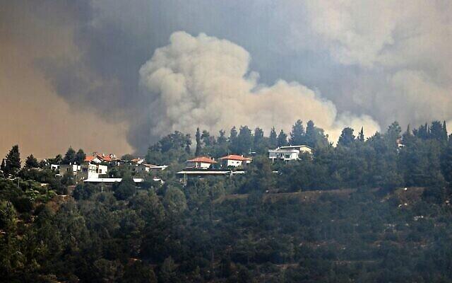De la fumée provenant d'un feu de forêt sur les collines de Jérusalem, près du Moshav Shoresh, le 16 août 2021. (Crédit : Ahmad GHARABLI / AFP)