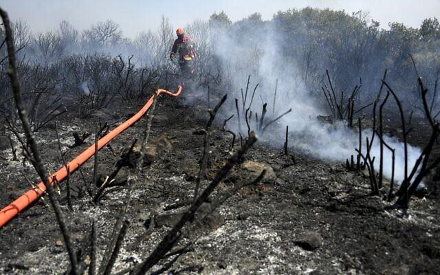 Les pompiers français utilisent un tuyau d'arrosage pour éteindre un incendie à Gonfaron, dans le département français du Var, dans le sud de la France, le 17 août 2021. (Photo par NICOLAS TUCAT / AFP)