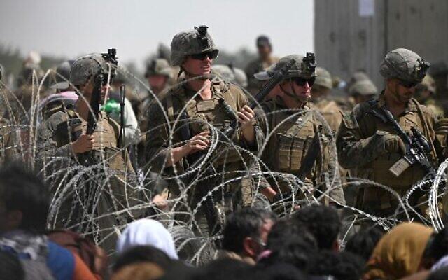 Des soldats américains montent la garde derrière des barbelés alors que des Afghans se trouvent au bord d'une route près de la zone militaire de l'aéroport de Kaboul, le 20 août 2021, dans l'espoir de fuir le pays après la prise de contrôle de l'Afghanistan par les talibans. (Crédit : Wakil KOHSAR / AFP)
