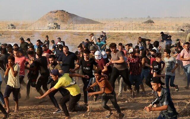 Des Palestiniens fuient les gaz lacrymogènes tirés par les forces de sécurité israéliennes le long de la barrière frontalière, à l'est de Khan Younis, dans le sud de la bande de Gaza, le 25 août 2021. (Crédit : Mahmud Hams/AFP)