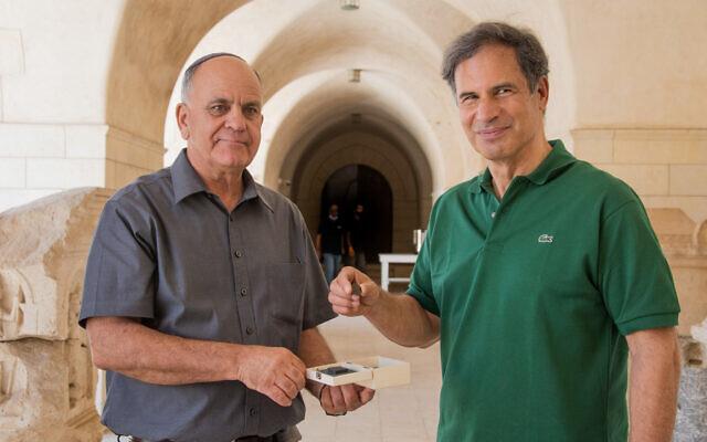 L'astronaute israélien Eytan Stibbe (à droite) tient une pièce de 1 900 ans datant de la révolte de Bar Kochba qu'il emportera dans l'espace, aux côtés d'Eli Eskosido, directeur de l'Autorité des antiquités d'Israël, en août 2021. (Crédit : Yoli Schwartz/Autorité des antiquités d'Israël)