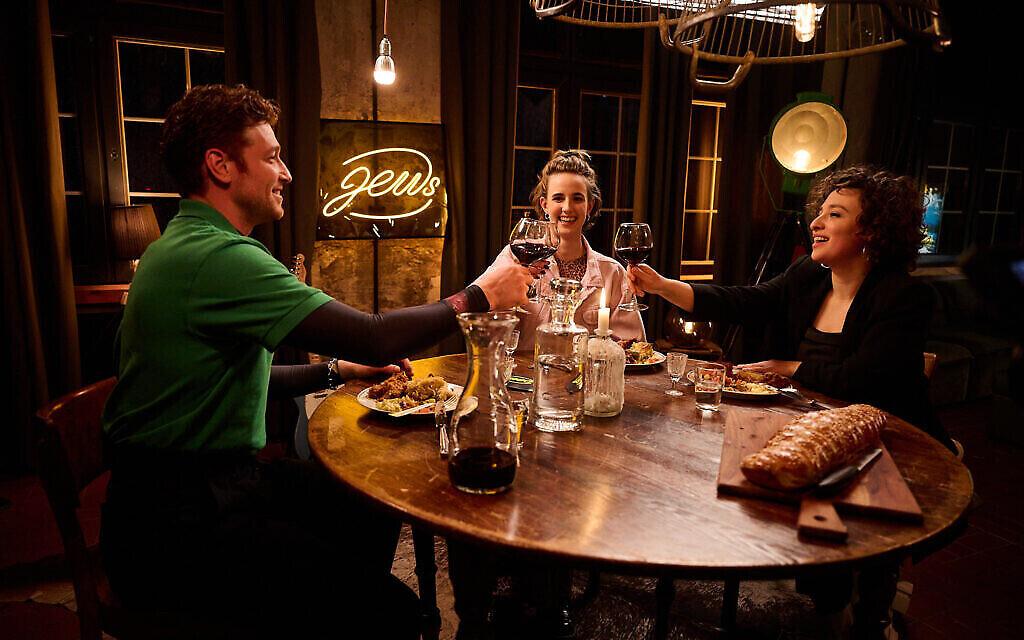 L'acteur Daniel Donskoy porte un toast avec les invités Helene Shani Braun, au centre, et Laura Cazes, dans « Freitagnacht Jews » en Allemagne. (Christian Pries / JTA)