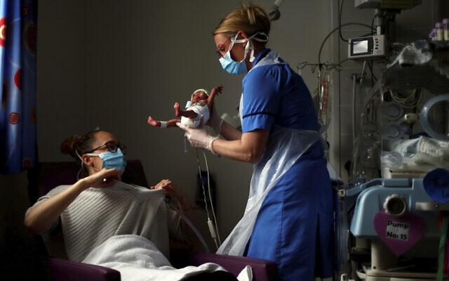 Illustration : une infirmière en néonatalogie remet un bébé à sa mère pendant la pandémie de coronavirus. (Crédit : Hannah McKay/Pool Photo via AP)
