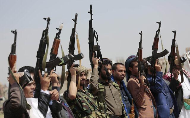 Des membres de tribus loyales aux rebelles houthis lèvent leurs armes pendant une manifestation contre l'accord de normalisation conclu entre Israël et les Émirats arabes unis, à Saana, au Yémen, le 22 août 2020. (Crédit : AP/Hani Mohammed, File)