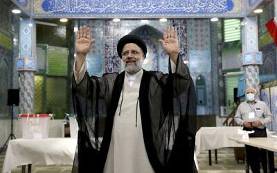 Ebrahim Raïssi, candidat aux élections présidentielles iraniennes, salue les médias après avoir voté dans un bureau de vote à Téhéran, en Iran, le vendredi 18 juin 2021. (Crédit : AP Photo/Ebrahim Noroozi)