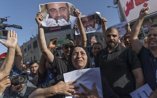 Maryam Banat, 67 ans, la mère de l'activiste Nizar Banat, critique de l'Autorité palestinienne, brandit sa photo pendant un rassemblement dénonçant sa mort entre les mains des services de sécurité de l'AP à Ramallah, en Cisjordanie, le 3 juillet 2021. (Crédit : AP Photo/Nasser Nasser)