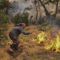 Une femme tente d'arrêter un incendie de forêt en progression dans le village de Kacarlar près de la ville côtière méditerranéenne de Manavgat, Antalya, Turquie, le samedi 31 juillet 2021. (Crédit : AP)