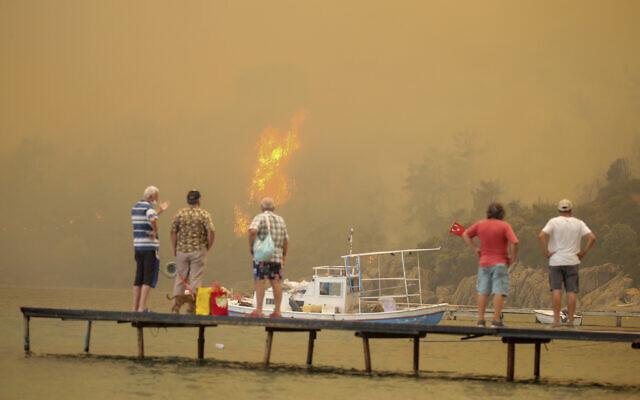 Des touristes attendent d'être évacués de la zone de Mazi, envahie par la fumée, alors que les feux de forêt descendent la colline vers le bord de mer, à Bodrum, Mugla, Turquie, le 1er août 2021. Plus de 100 incendies de forêt ont été maîtrisés en Turquie, selon les autorités. (Crédit : AP Photo/Emre Tazegul)