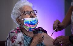 Rachel Gershon, 83 ans, reçoit une troisième dose de vaccin Pfizer-BioNTech administrée par un bénévole du Magen David Adom dans une maison de retraite de Netanya, le 1er août 2021. (Crédit : AP Photo/Oded Balilty)