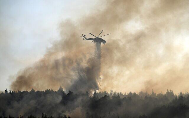 Un hélicoptère largue de l'eau sur un incendie dans la zone de Varibobi, au nord d'Athènes, en Grèce, le 4 août 2021. (Crédit : AP Photo/Thanassis Stavrakis)