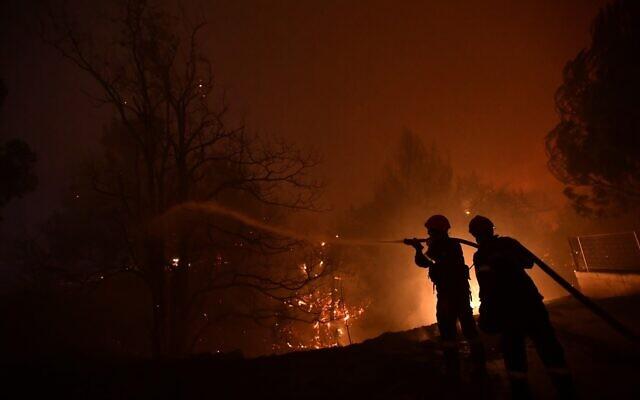 Des pompiers tentent d'éteindre un feu de forêt dans la région d'Afidnes, au nord d'Athènes, en Grèce, le jeudi 5 août 2021. (Crédit : AP/Michael Varaklas)