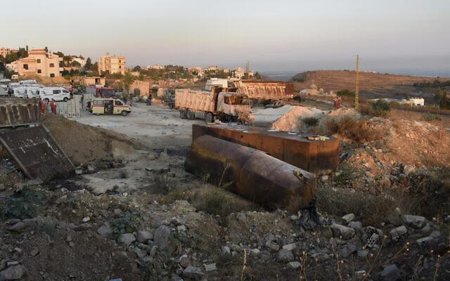 Des secouristes et des soldats libanais se rassemblent sur les lieux où un camion-citerne a explosé, dans le village de Tleil, au nord du Liban, dimanche 15 août 2021. (Crédit : AP)