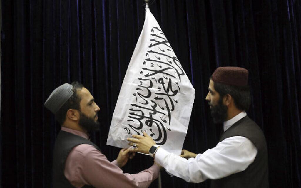 Des responsables talibans installent un drapeau taliban avant une conférence de presse du porte-parole des Talibans Zabihullah Mujahid, au Government Media Information Center à Kaboul, en Afghanistan, le 17 août 2021. (AP Photo / Rahmat Gul)