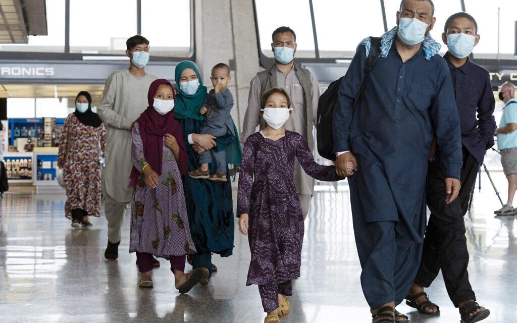 Des familles évacuées de Kaboul, en Afghanistan, traversent le terminal avant de rejoindre un bus à leur arrivée à l'aéroport international Washington Dulles de Chantilly, en Virginie, le 23 août 2021. (Crédit : AP Photo/Jose Luis Magana)