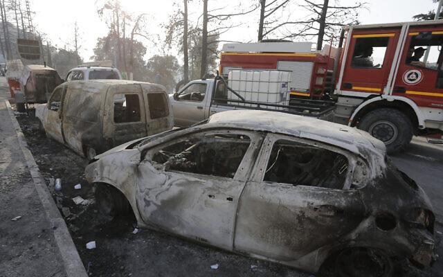 Des voitures calcinées sont photographiées après un incendie près du village d'Achlouf, dans la région de la Kabylie, à l'est d'Alger, le 13 août 2021. (Crédit : Toufik Doudou/AP)