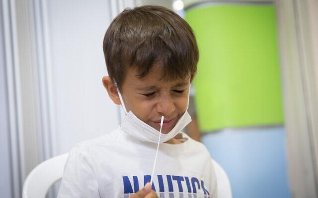 Des enfants prélèvent des échantillons dans le cadre d'un test de dépistage du coronavirus à l' hôpital Sheba pour les étudiants qui retournent à l'école au début de la nouvelle année scolaire. (Crédit : Miriam Alster/Flash90)