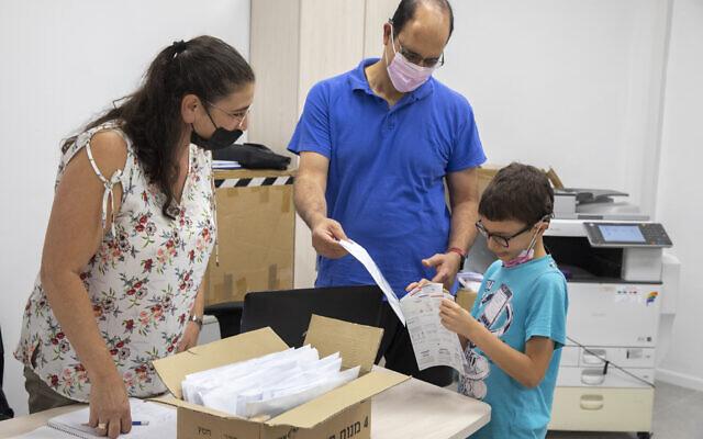 """Des parents et des enfants de l'école """"Cramim"""" reçoivent un test COVID-19 en kit à domicile avant l'ouverture de la nouvelle année scolaire, à Jérusalem, le 30 août 2021. (Crédit : Olivier Fitoussi/Flash90)"""