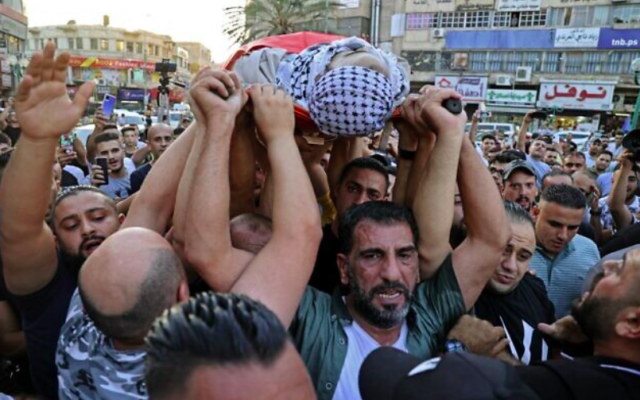 Des Palestiniens portent le corps de Dia al-Sabarini, 25 ans, lors de ses funérailles dans la ville de Naplouse, en Cisjordanie, le 11 août 2021. (JAAFAR ASHTIYEH / AFP)