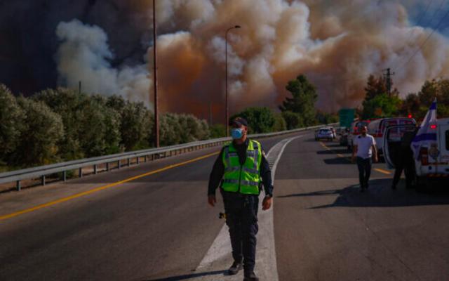 Des pompiers sur le site d'un feu de forêt à l'ouest de Jérusalem, le 15 août 2021. (Crédit : Yonatan Sindel/Flash90)