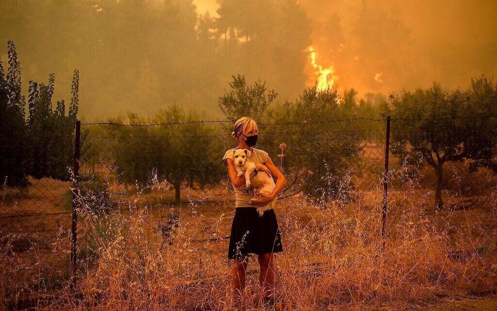 Une femme tient un chien dans ses bras alors que des feux de forêt approchent du village de Pefki sur l'île d'Evia (Eubée), la deuxième plus grande île de Grèce, le 8 août 2021. (Crédit : ANGELOS TZORTZINIS/AFP)