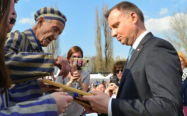 Edward Mossberg, survivant de la Shoah, rencontre le président polonais  Andrzej Duda, lors d'une cérémonie de la Marche des Vivants dans le camp d'extermination d'Auschwitz-Birkenau en Pologne, alors qu'Israël célèbre Yom HaShoah, le 12 avril 2018. (Crédit : Yossi Zeliger/ Flash90/ File)